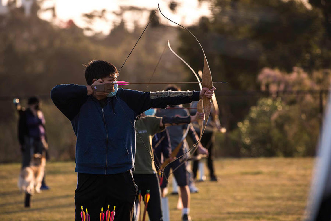 Student taking part in an archery class