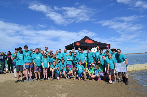 A large group of people standing on a beach wearing matching turquoise shirts