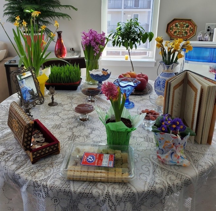 An image of a table with sweets, coins, flowers, books, and treats on it.