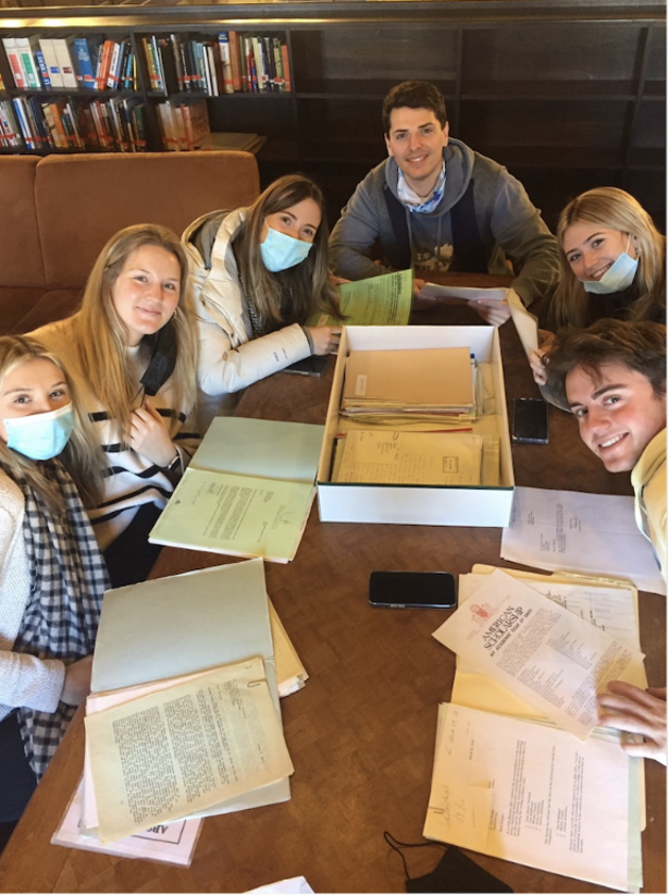 students with archival documents and boxes on tabletop