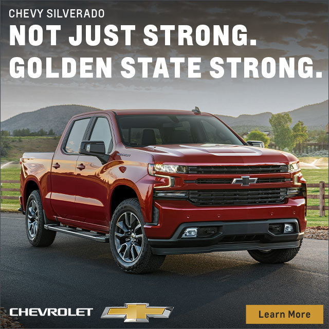 Chevrolet Silverado on a road withmountains and fields behind it