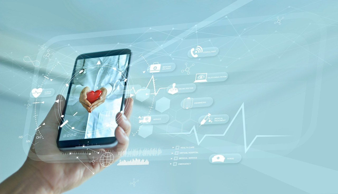 Image of person holding a mobile phone, screen is a medical professional with stethoscope and heart in hand.