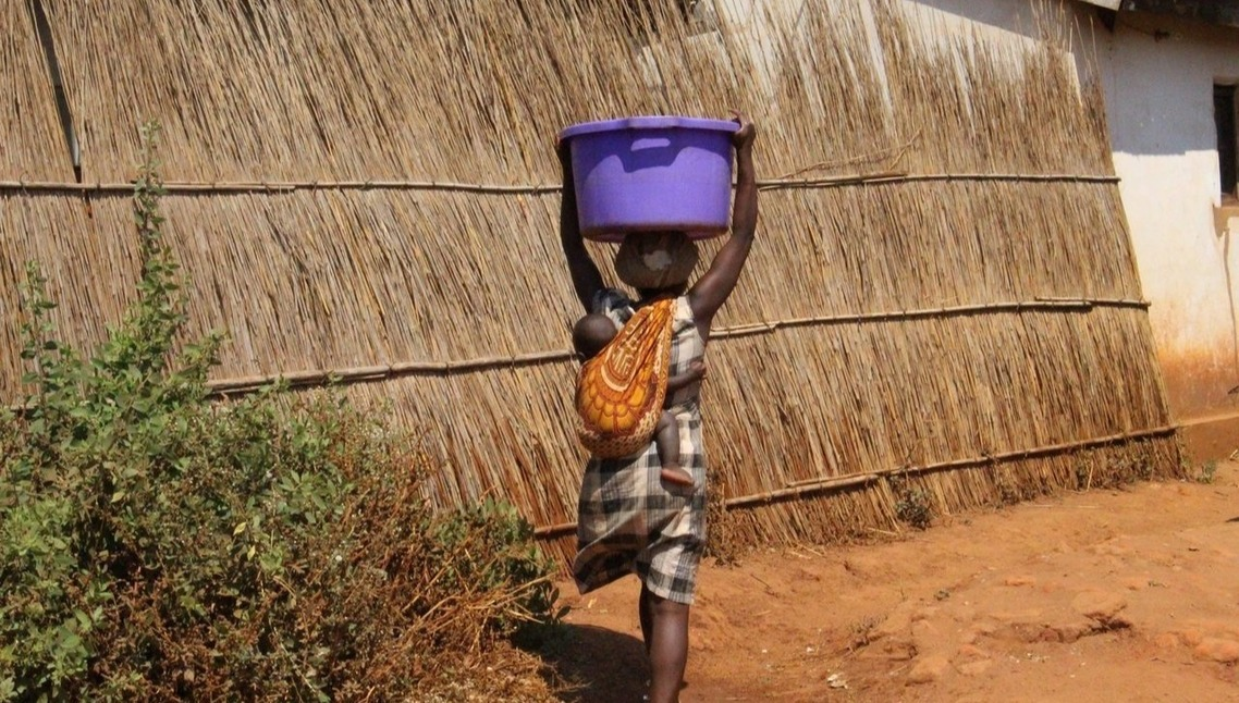Photo of woman in Malawi carrying a large vessel fo water on her head and a baby on her back.