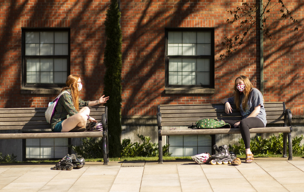 A pair of campus rollerbladers take a break along Commencement Walk to chat and soak up the early spring sunshine.
