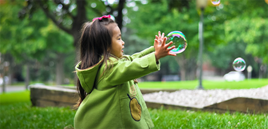 Girl trying to catch a bubble, link to tips for toddler play