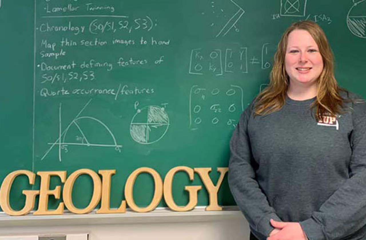 Student Susan Adams stands next to a chalk board that has been filled with geology teaching notations and has large alphabet letters spelling out the word geology set on the chalk tray at the bottom of the chalk board.