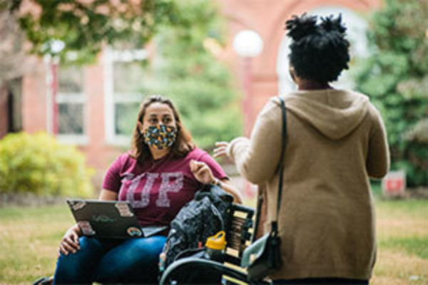 masked student sitting on a bench with laptop talking to another student standing