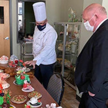 Academy of Culinary Arts member shows Congressman Glenn Thompson a spread of prepared dishes