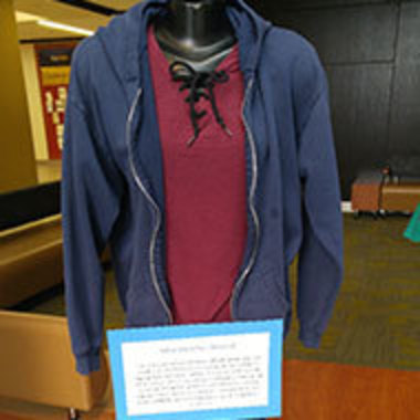headless mannequin wearing shirt and hoodie with explanation attached