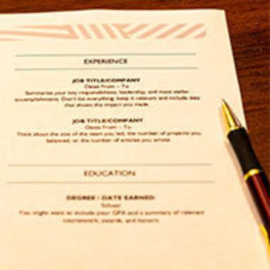 closeup of résumé and stylish pen resting on desk
