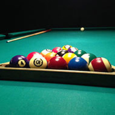 closeup of pool table with balls in rack