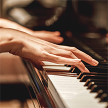 closeup of hands of person playing a piano
