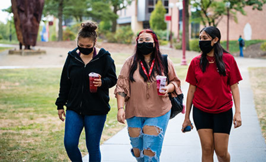 three masked students walking together through Oak Grove with World Trade Center remnant, humanities building, and library in the background