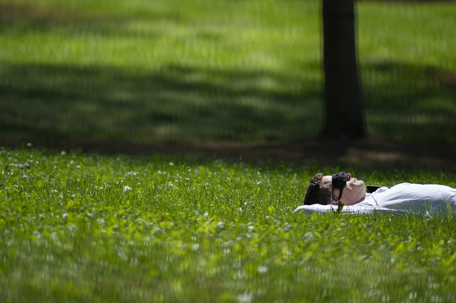 A student sleeping in the grass in the groove