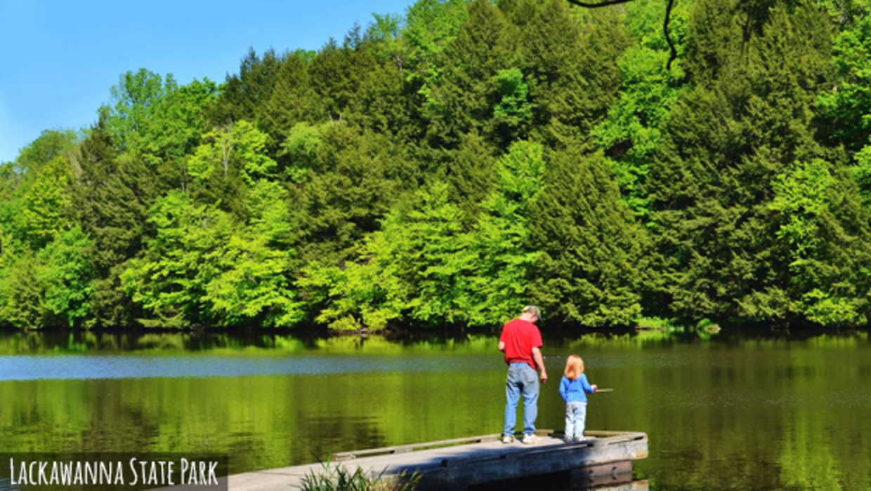 A man with his young daughter fishing on the edge of a lake in Lackawanna State Park