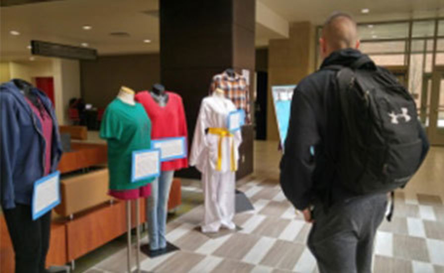 """a student looks at the display of clothing and survivor stories from a previous year's """"What Were You Wearing?"""" exhibit"""