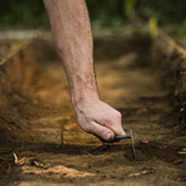 closeup of hand scraping away dirt during archaeological dig