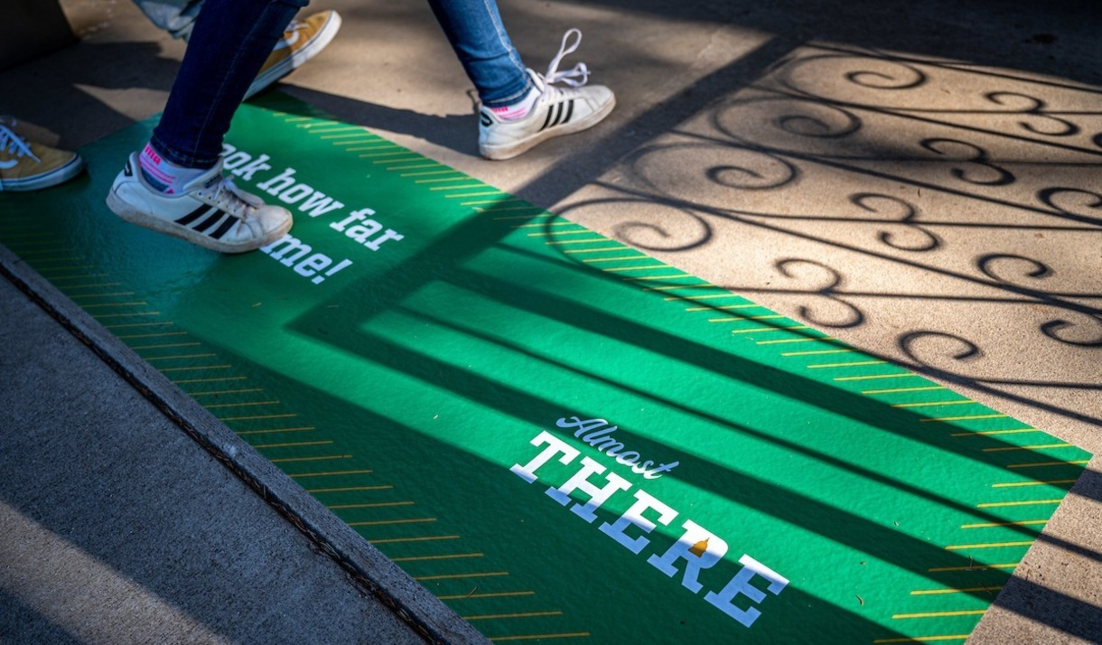 Photo of student stepping on painted sidewalk that says,