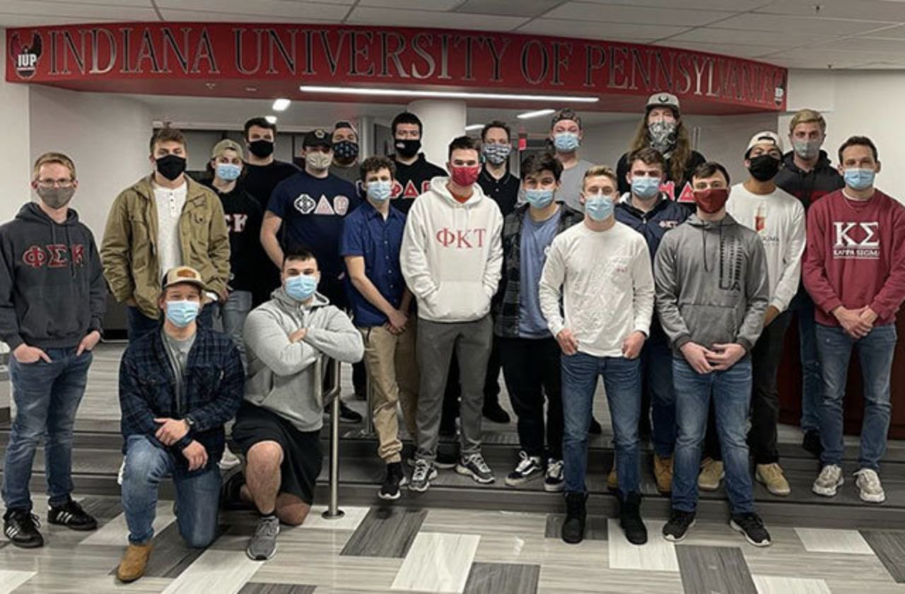 a group of about 20 male students posing, some with fraternity letters on their shirts, all with masks, in the lobby of the Center for Multicultural Student Leadership and Engagement, with the lobby's