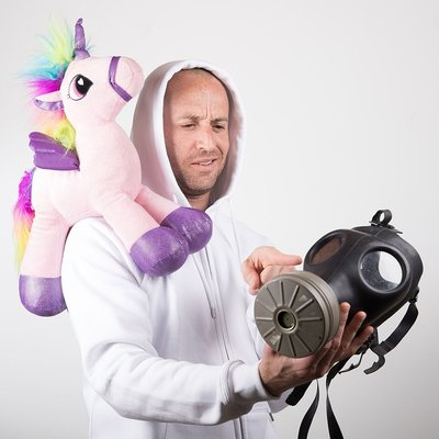Jimbo J with stuffed unicorn on his shoulder holding gas mask in white hoodie