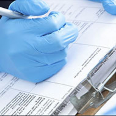 hands with medical gloves writing on a clipboard