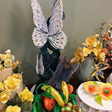 display of sugar sculptures including a butterfly, flowers, and a bowl of fruit
