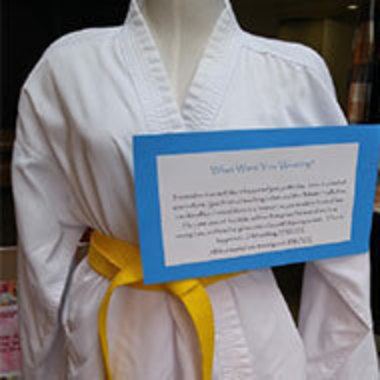 martial arts uniform with yellow belt on mannequin with survivor story attached