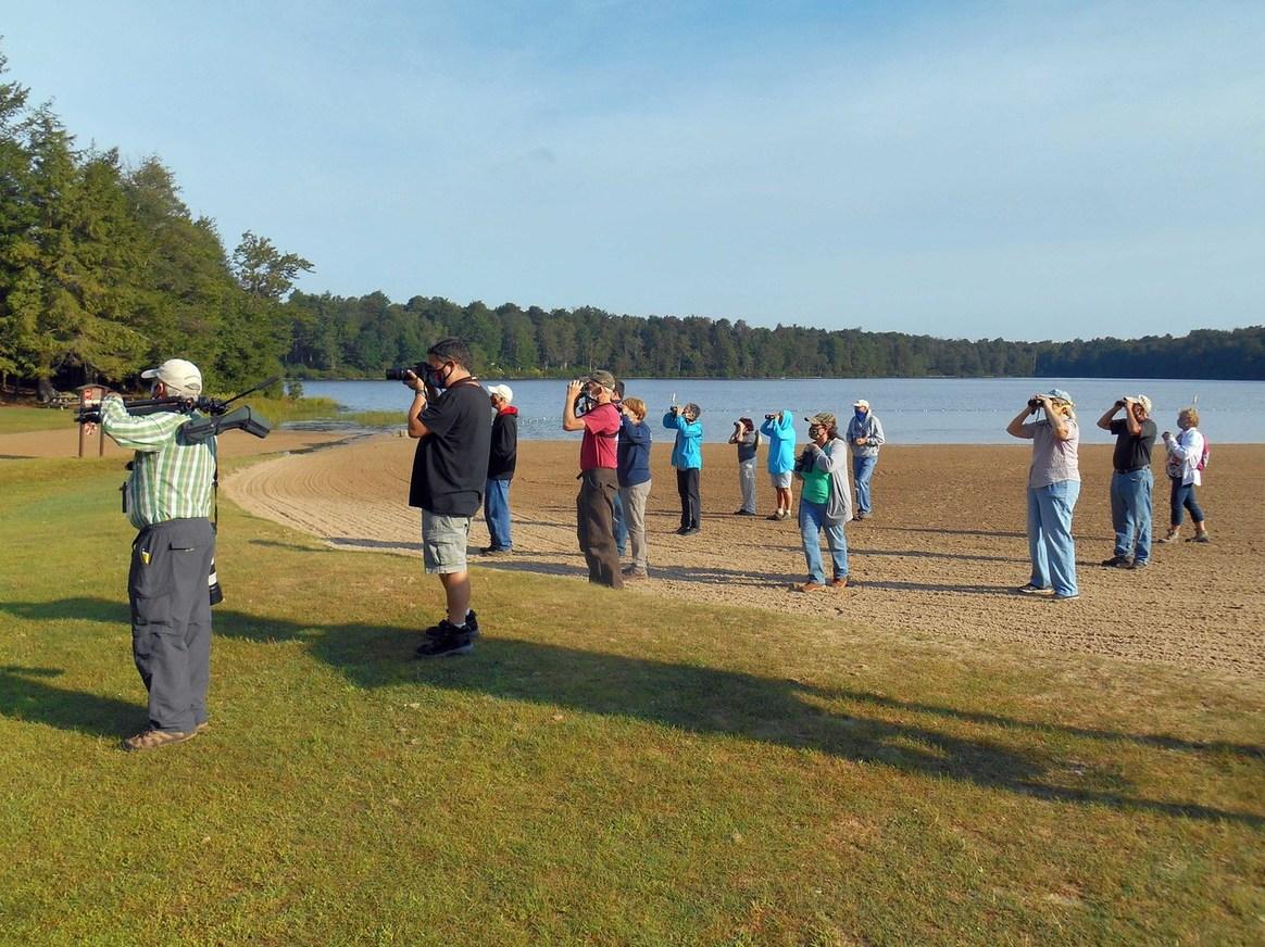 People, grass, lake, cameras, binoculars, trees, outside.