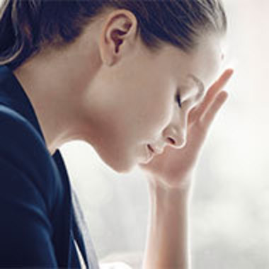 stressed-looking woman holding her head