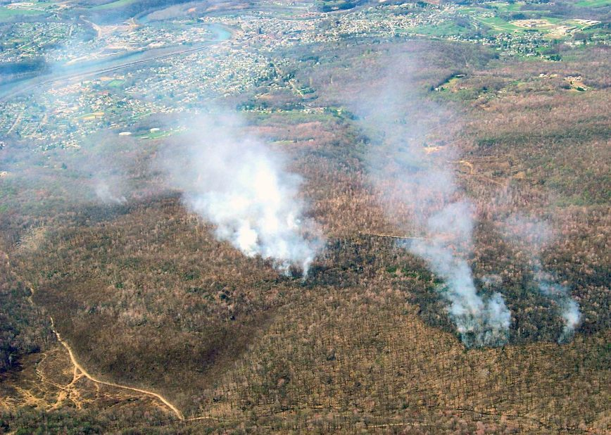 Aerial view, smoke, mountains, trees, roads, houses