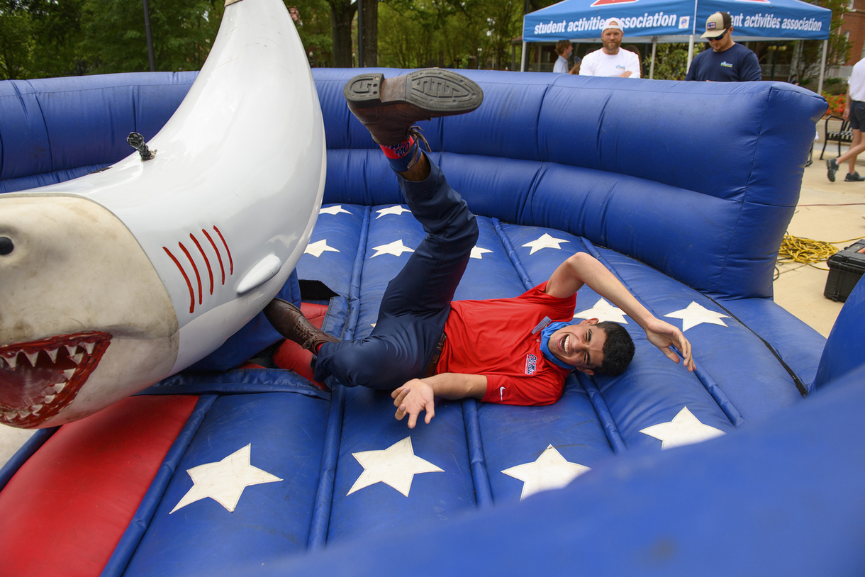 Student falling off mechanical shark laughing