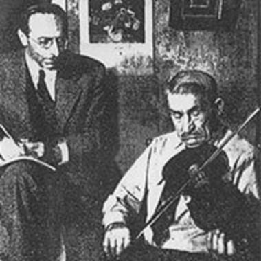black-and-white image of Samuel Bayard transcribing music as a fiddler plays