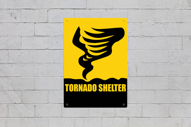 Brick wall with sign with a tornado and