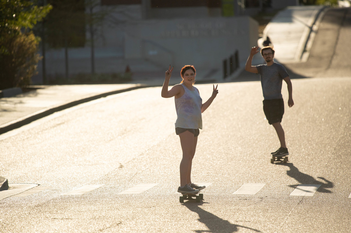 Students skateboarding down the road on campus