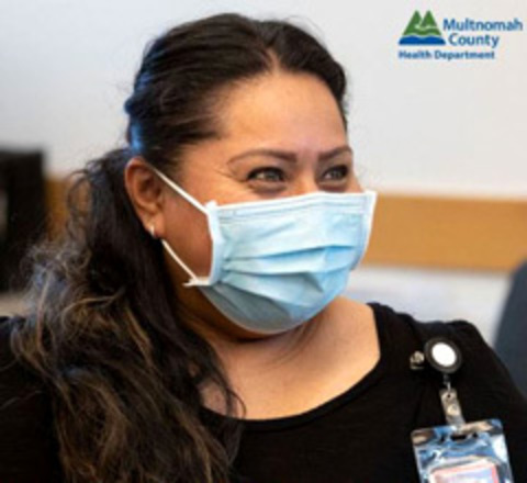 A Latino woman assists the COVID 19 vaccine effort.