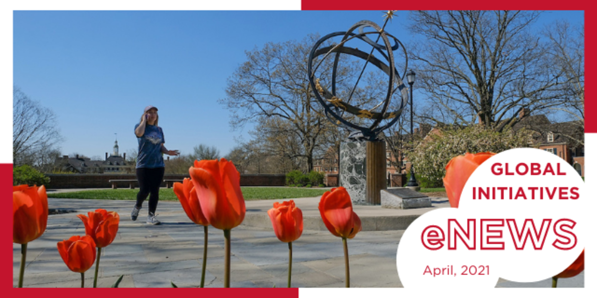 Student on phone walks near sundial, with red tulips in foreground