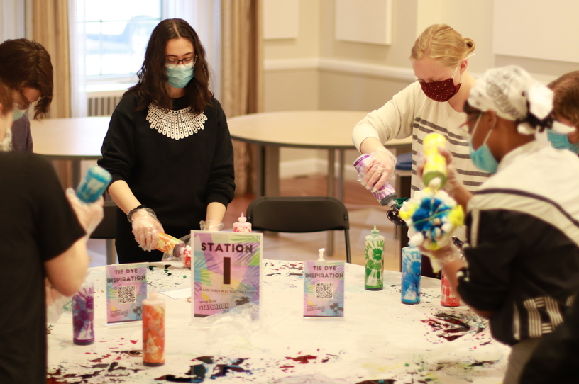 Students standing around a table and tie-dyeing shirts