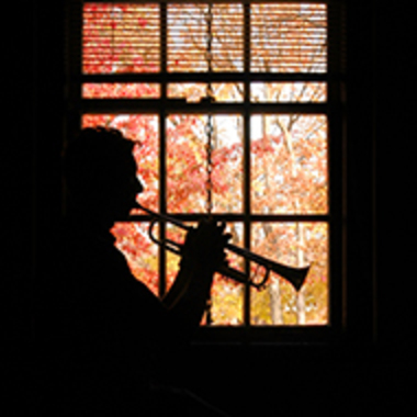 A silhouette of a person playing the trumpet in front of a window.