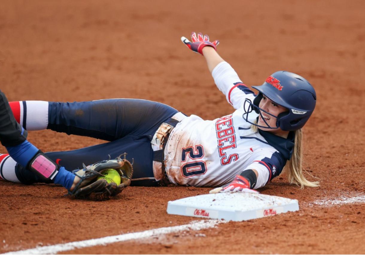 Softball player sliding into base