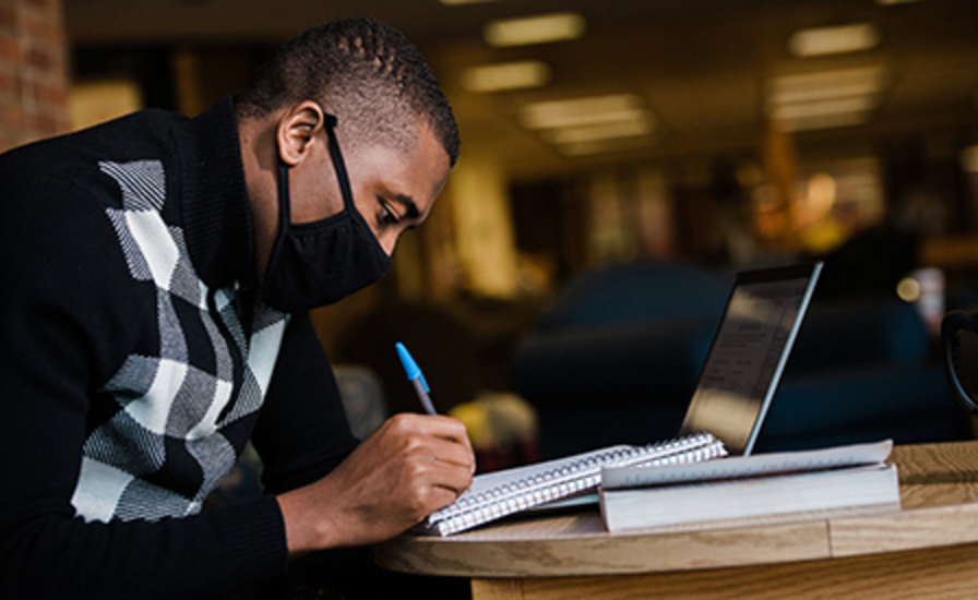 A student writes in a notebook while looking at his laptop in the library, wearing a mask.