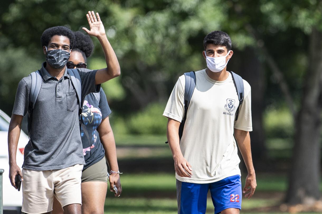 Students walking wearing masks and waiving at the camera