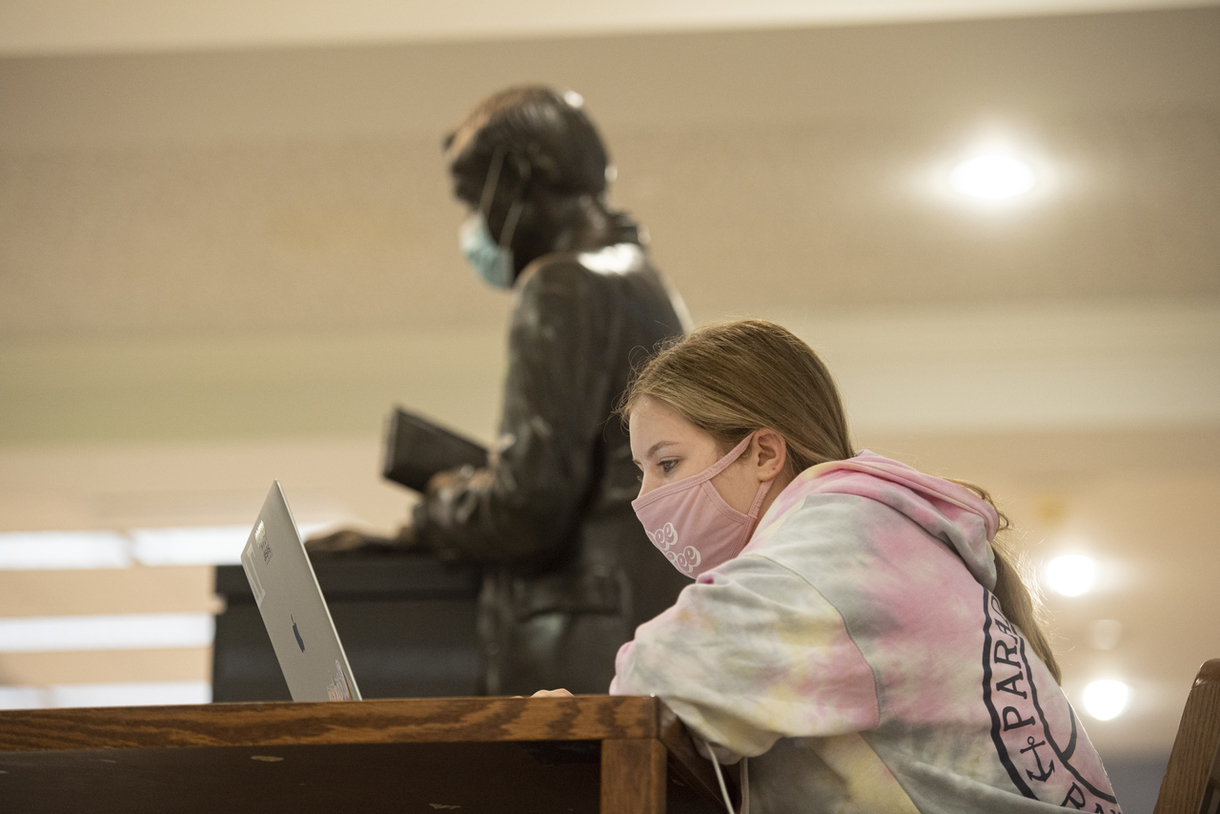 Student wearing mask on her computer in the library