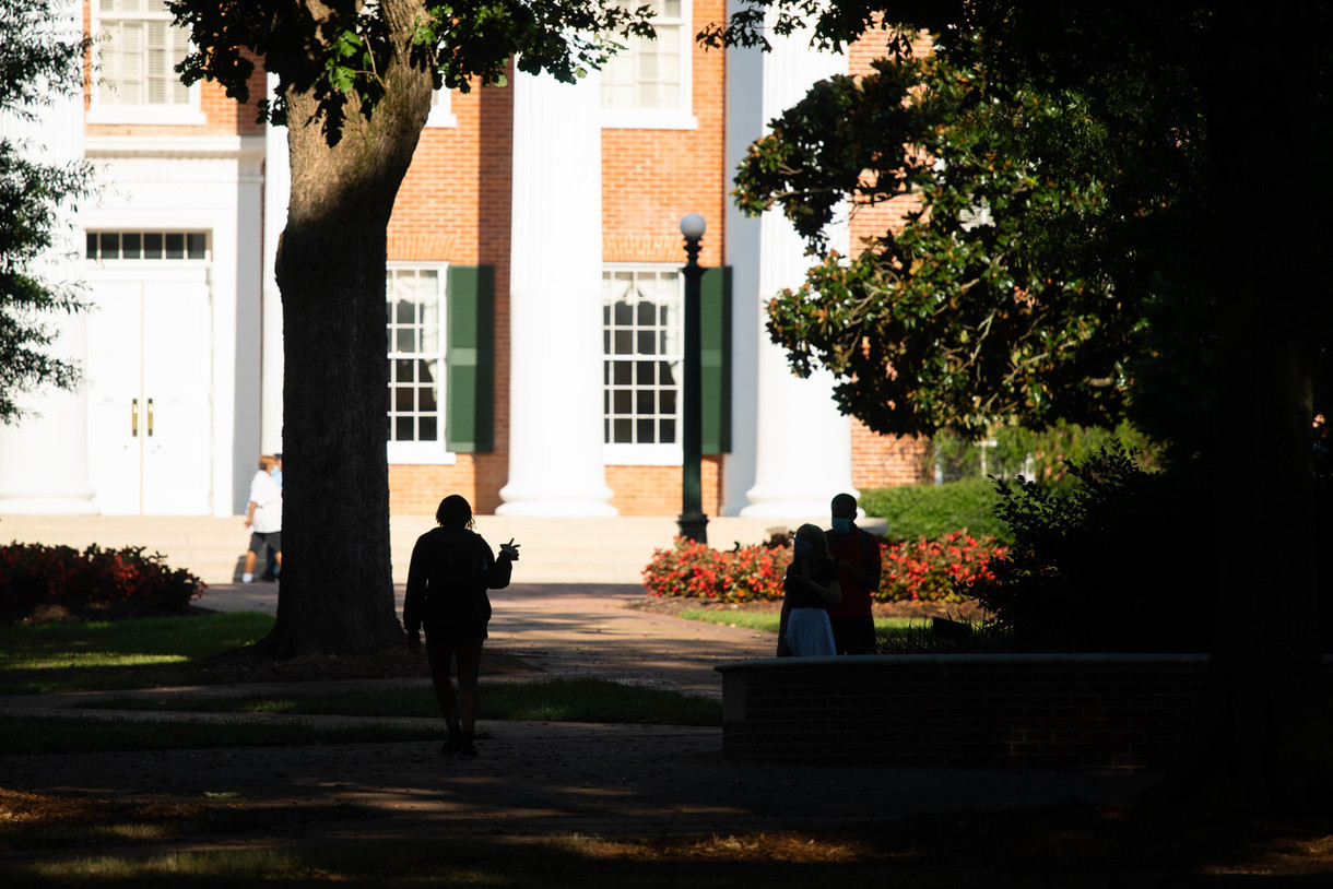 Silhoute of students outside the lyceum in shaded area