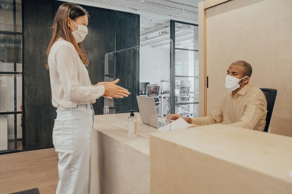 Two people wear masks in an office