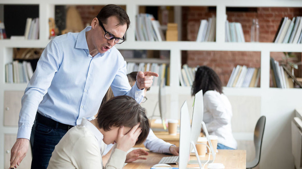 Photo of boss talking sternly to staff member