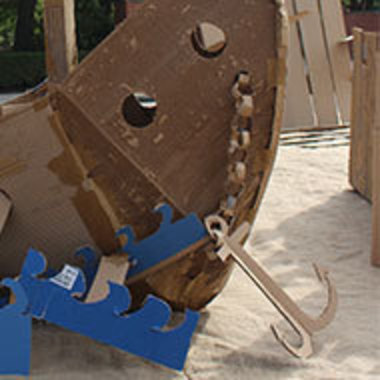 detail of cardboard ship with anchor resting on sand