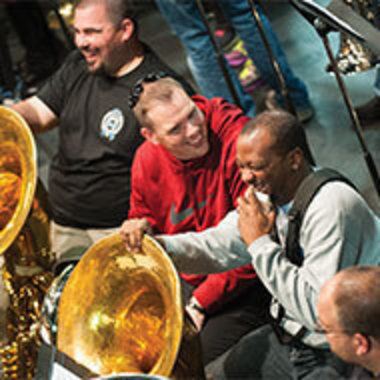 Tuba players share a laugh at a rehearsal during the 95th marching band reunion in 2016