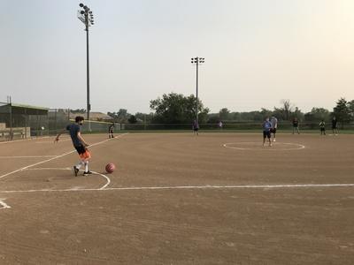 man kicking a kickball on a baseball field