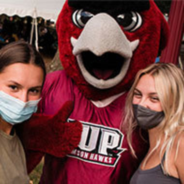 IUP mascot Norm posing with two masked students