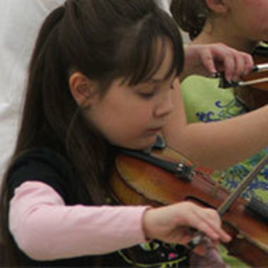 young girl playing the violin during instruction